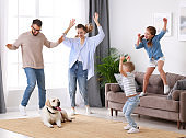 Playful family dancing in living room with dog