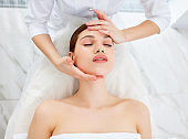 Therapist doing myofascial or buccal massage on face and head fo