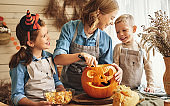 Happy family mother and kids carving pumpkin for Halloween holid