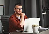 Thoughtful businessman working on laptop computer remotely at home