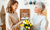 Delighted young woman congratulations mother with bouquet of fresh tulips