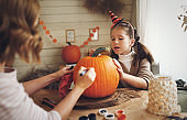 Happy mother and daughter making jack-o-lantern together in kitchen, drawing scary face on pumpkin