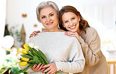 Delighted young woman hugging mother with bouquet of fresh tulips