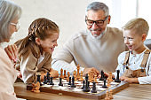 Children brother and sister playing chess while sitting in living room with senior grandparents