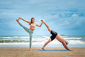 Young healthy Yoga woman and man workout yoga pose on the beach at daytime