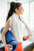 Tired, but Happy: Fit  Woman Wiping her Face with a Towel after a Home Workout