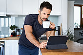 Worried man having morning coffee using digital tablet