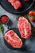 Raw top blade oyster Steak on stone and meat butcher cleaver, marbled beef with herbs tomatoes peppercorns over grey stone surface background  top view vertical