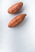 Raw whole sweet potatoe on white background, flat lay with copyspace