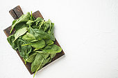 Young raw spinach, on wooden cutting board, on white stone  background, top view flat lay, with copy space for text
