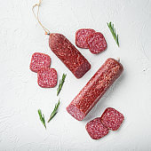 Salami with herbs , garlic , square format, on white stone table background, top view flat lay
