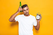 Image of brunette man 30s in white t-shirt drinking beer and holding alarm clock while standing isolated