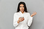 Photo of shocked or outraged woman 30s in formal wear looking on camera while holding smartphone in hand, isolated over gray background