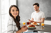 Portait of joyous man and woman 30s having breakfast or dinner in gray apartment, while sitting at table in kitchen