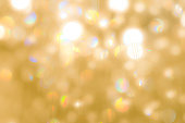 Blur yellow gold bokeh background of reflective glittering light from holiday party crystal ball chandelier