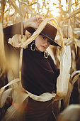 Stylish woman in hat and brown outfit posing in autumn maize field in warm sunny light. Fashionable attractive young female with confident look standing in corn in fall season in countryside