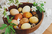 Stylish easter eggs in wooden bowl on rustic table with spring flowers anemones. Happy Easter!