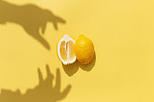 Two halved cuts of lemon with shadow from hand on yellow background