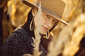 Beautiful stylish woman in brown hat and vintage coat posing in autumn maize field in sunset light. Portrait of fashionable young hipster female standing in autumnal corn in evening countryside