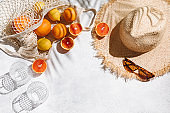 Summer fashion flat lay on white background. Holiday party, vacation, travel, tropical concept. Straw hat, sunglasses, glass and citrus fruits. Palm shadow and sunlight, sun. Top view, copy space.