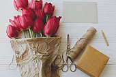 Red tulips in craft paper with greeting card, gift, pencil, scissors on white wood. Mothers day