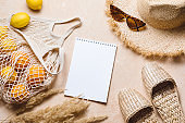 Summer flat lay on beige background. Straw hat, sunglasses, slippers and lemons in eco friendly mesh shopping bag. Summer travel fashion concept
