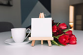 Bouquet of red tulips, coffee cup, empty white frame. Concept for greeting card