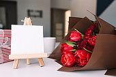 Red tulips bouquet, coffee cup, empty white frame, pink gift box, greeting card