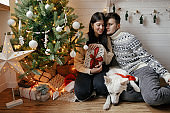 Stylish couple with cute dog holding christmas gift with red bow on background of christmas tree in lights in festive decorated room. Young family with pet exchanging present. Merry Christmas!