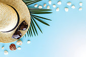Travel, vacation concept. Hat, sea shells, palm, eyeglasses on blue background