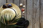 Travel, vacation concept. Straw hat, palm leaf, eyeglasses, sea shells, shoes