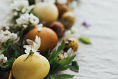 Easter eggs with spring flowers and tender petals on rustic linen. Aesthetic eco natural holiday