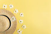 Summertime concept on yellow background, straw hat and flower heads of daffodil