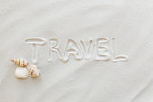 Travel, vacation concept. Sea shells on sand and blue background. Travelling