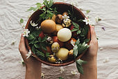 Happy Easter! Easter eggs and spring flowers in wooden bowl in hands on rustic linen. Aesthetic