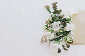Roses, hydrangea, and eucalyptus branches growing from craft envelope on white wood, copy space