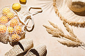 Summer flat lay on beige background. Straw hat, sunglasses, slippers and lemons in eco friendly mesh shopping bag. Palm shadow and sunlight, sun. Minimal summer travel fashion concept