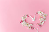 Flat lay on pink background with apple blossom heart shape and earphones