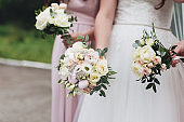 Bride in white dress is holding wedding bouquet with bridesmaids
