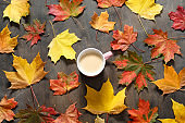 Autumn mood flat lay. Cup of coffee with maple leaves on dark wooden background. Autumn holidays, family celebration, thanksgiving day, home weekend, warming drink.