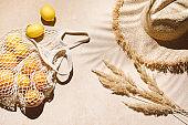 Summer flat lay on beige background. Straw hat and lemon fruits in eco friendly mesh shopping bag. Trendy palm shadow and sunlight, sun. Minimal summer travel fashion concept