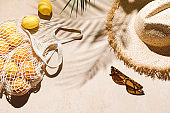 Summer flat lay on beige background. Straw hat, sunglasses, lemon fruits in eco friendly mesh shopping bag. Trendy palm shadow and sunlight, sun. Minimal summer travel fashion composition