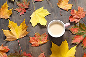 Autumn mood flat lay. Cup of coffee with maple leaves on dark wooden background. Autumn holidays, family celebration, thanksgiving day, home weekend, warming drink. Flat lay, top view, copy space.