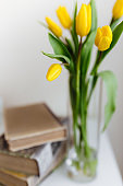 Bouquet of yellow tulip flowers in vase and books. Greeting card concept