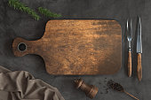 Old Wooden cutting board and Kitchen utensils on a Concrete background, Free space for your text