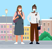 People wearing masks walk in the city to protect themselves from viruses. Masked women talking