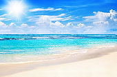 Beautiful tropical sand beach view, exotic island landscape, turquoise sea water ocean wave sun blue sky white cloud background, summer holidays vacation travel, Caribbean nature, Maldives, Seychelles