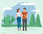 Couple walking in a park. Young guy and girl holding hands walking in summer garden, romantic walk