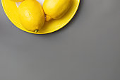 Yellow lemons on yellow plate on gray background. Colors of the Year 2021 Pantone Illuminating and Ultimate gray