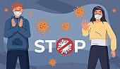 Young girl and guy in medical masks show stop gesture at background of flying virus, coronavirus